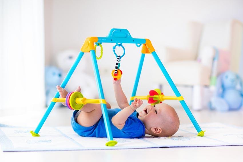 Bábätko na podložke sa hrá s detskou hrazdičkou