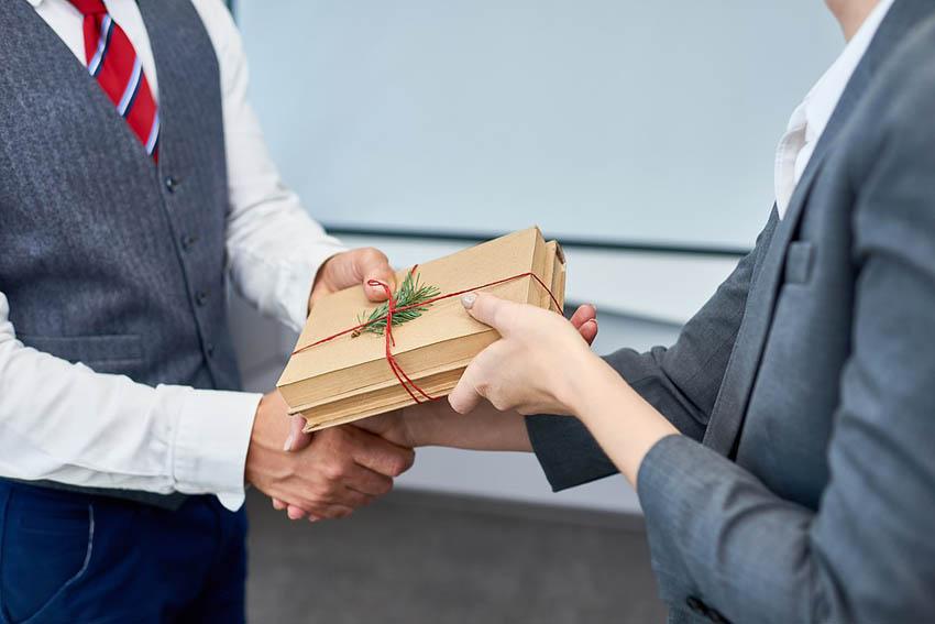 obchodní partneri si odovzdávajú vianočný darček