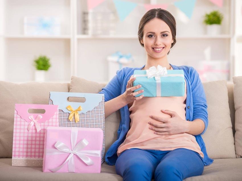 Tehotná mladá žena s darčekmi