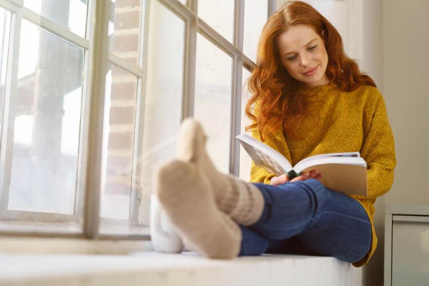 ryšavé dievča číta knihu na parapete