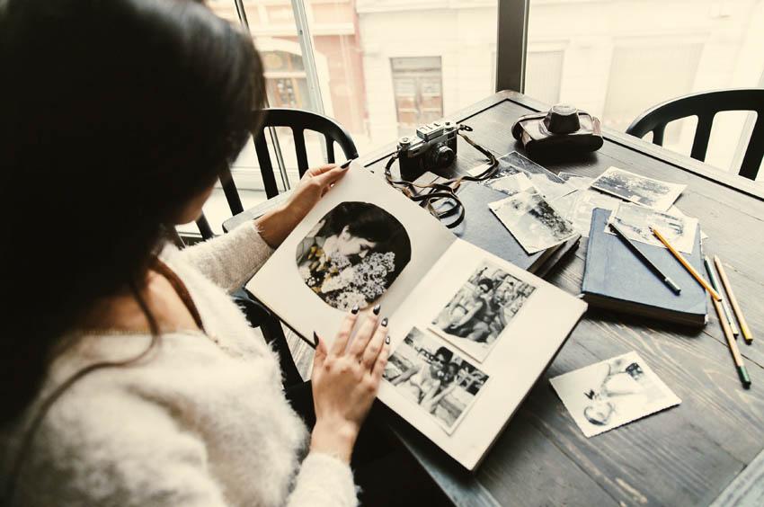 žena si prezerá fotoalbum s čiernobielymi fotkami