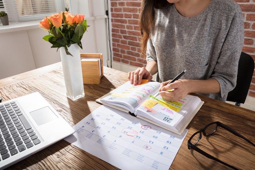žena za stolom, na ktorom má diár a kalendár