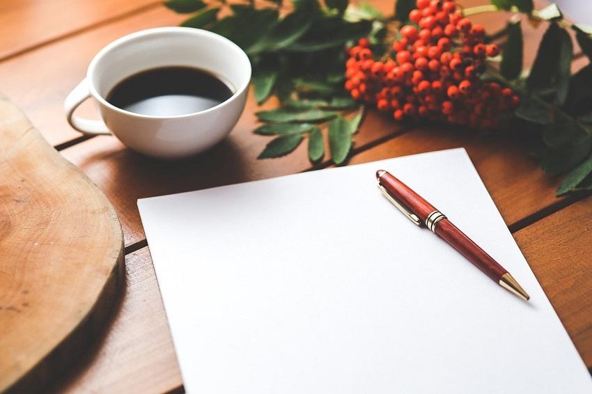 Pracovný stôl a na ňom šálka s kávou, pero a hárok papiera určeného na tlač dokumentov