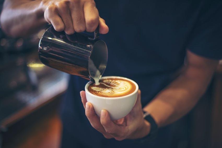 muž leje mlieko do kávy