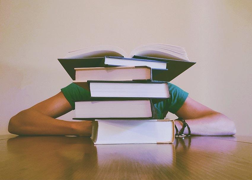 Študent a knihy ležiace na stole