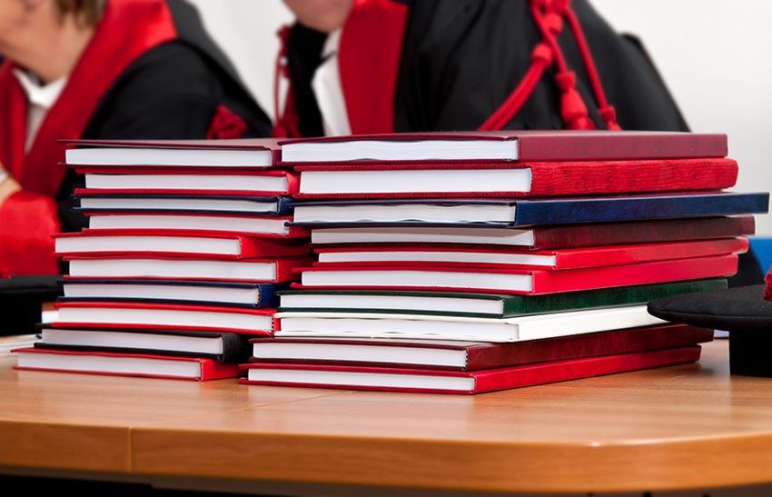 Štós farebných záverečných prác na stole profesorov