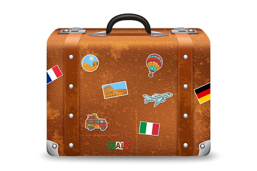 cestovný kufor olepený samolepkami