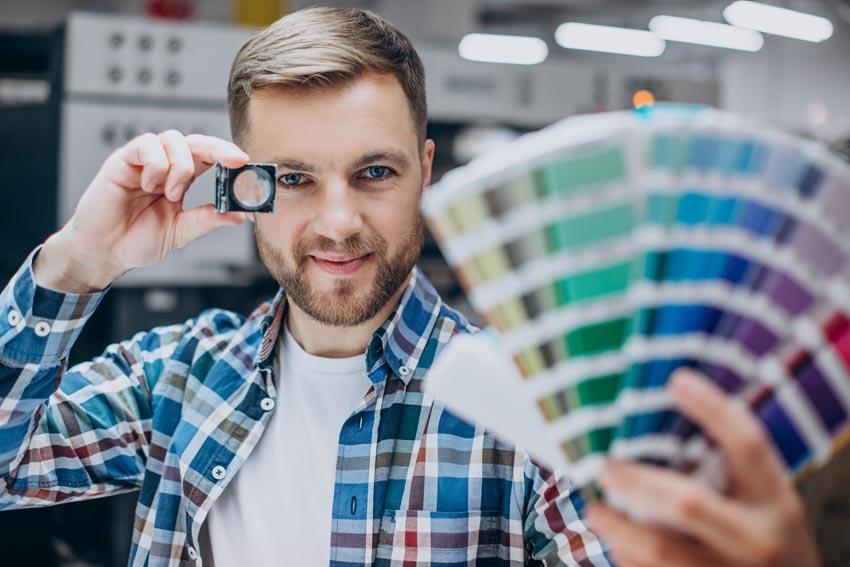 muž pozerá na farby vytlačených vzoriek
