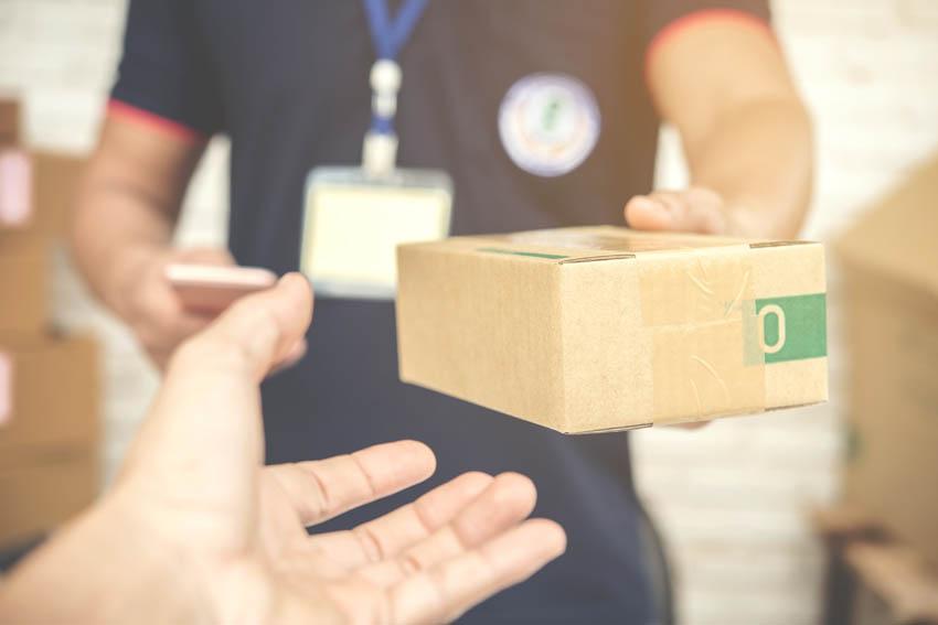 kuriér odovzdáva balík zákazníkovi