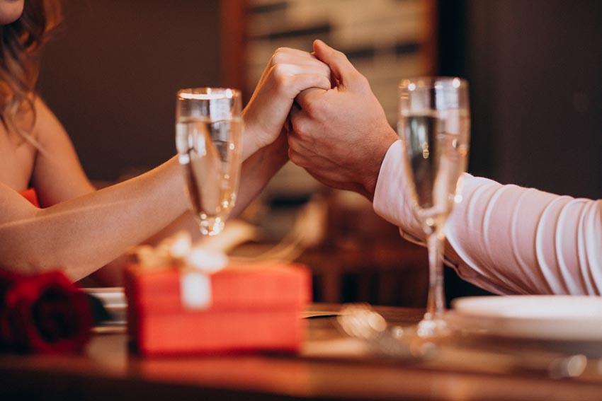 pár sa drží za ruky pri večeri