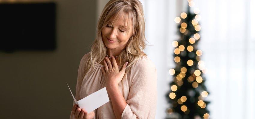 Staršia žena číta vianočnú pohľadnicu a usmieva sa