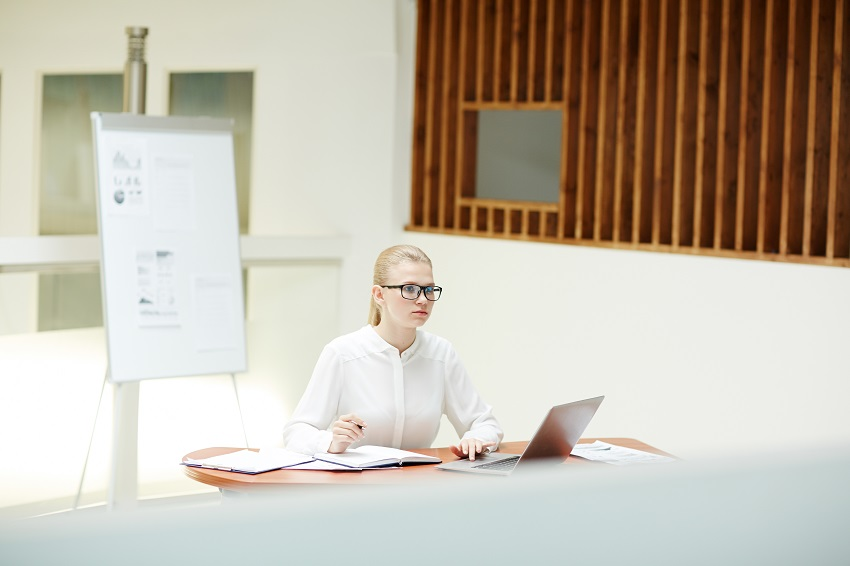Mladá žena sedí za stolom s laptopom a papiermi a pracuje na písaní svojej diplomovky