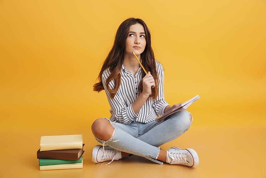 Dievča sedí na zemi a premýšľa pri písaní svojej záverečnej diplomovej práce
