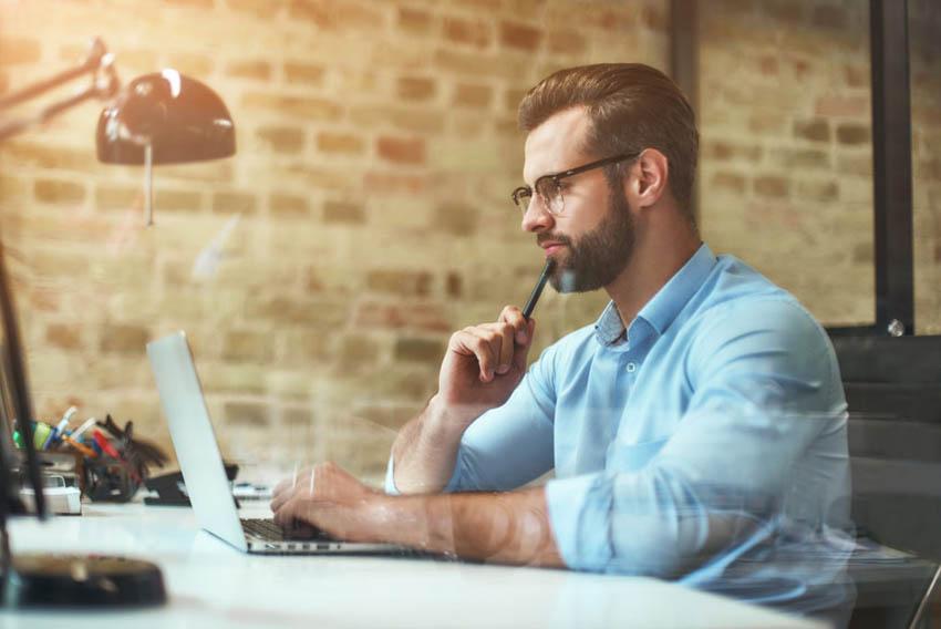 rozmýšľajúci muž za stolom a počítačom