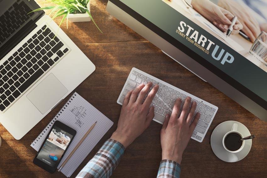 pracovný stôl s notebookom, monitorom, mobilom, zápisníkom a kávou