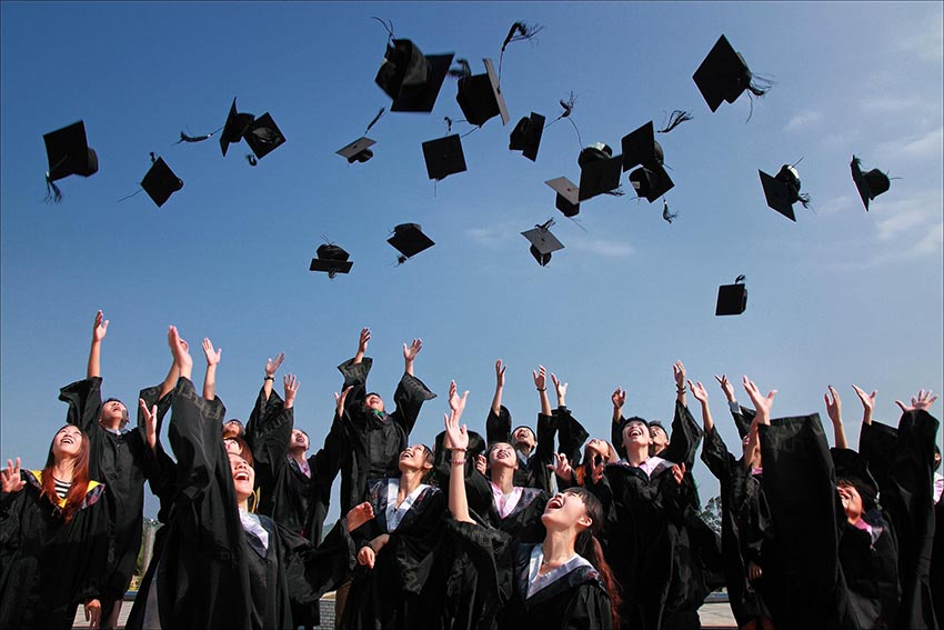študenti vyhadzujú čiapky nad hlavu