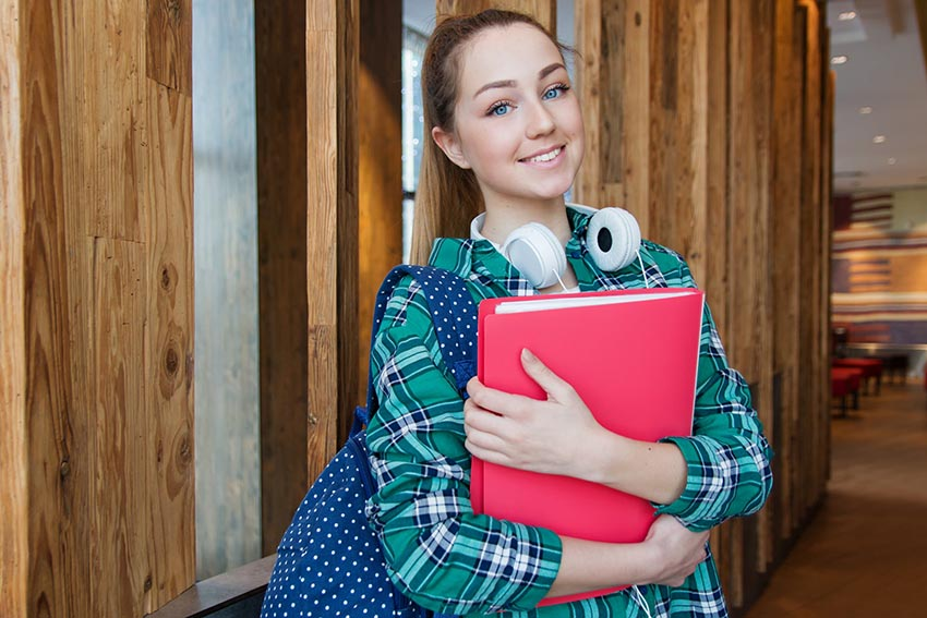 usmievavá študentka držiaca knihy