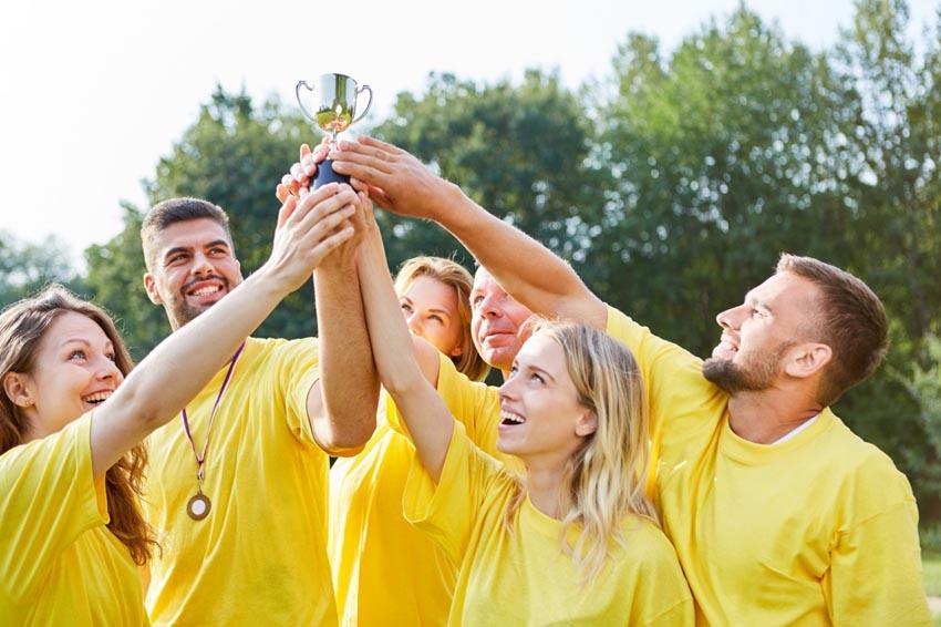 ľudia v žltých tričkách spoločne držia trofej