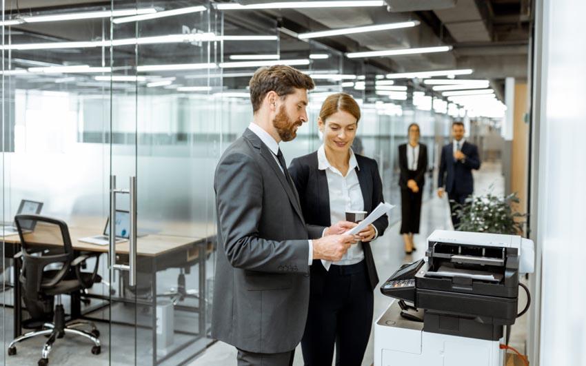 muž a žena stoja pri kopírke v kancelárii