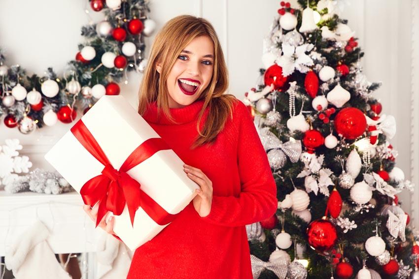 žena s darčekom pri vianočnom stromčeku