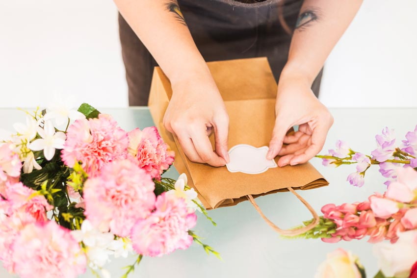 žena lepí prázdnu etiketu na papierovú tašku
