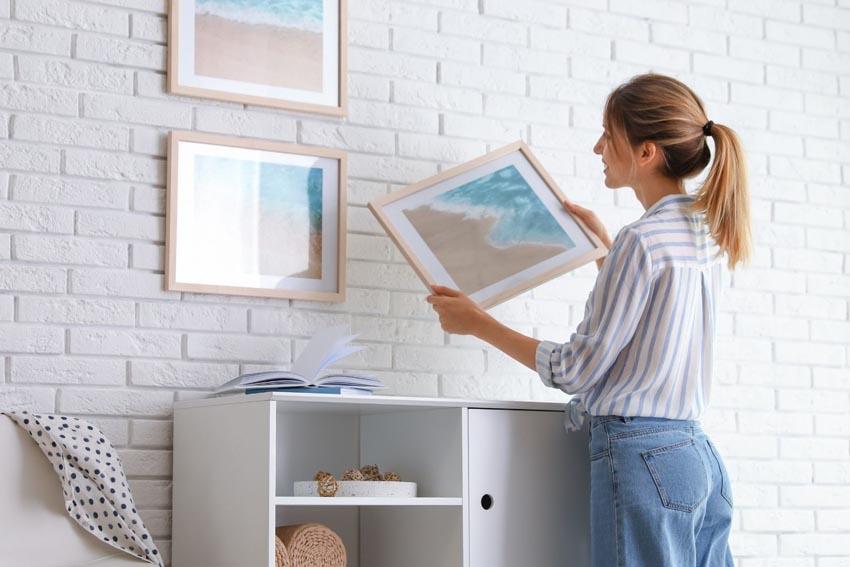 žena vešia obrazy na stenu
