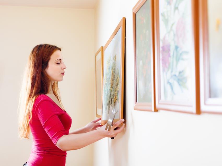 žena vešia obraz na stenu
