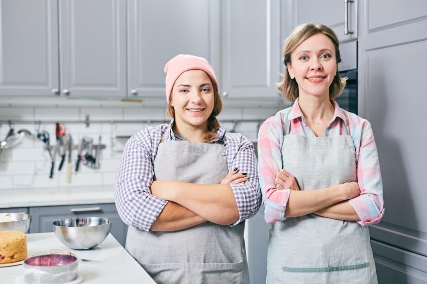 mladá žena s mamou v kuchynských zásterách