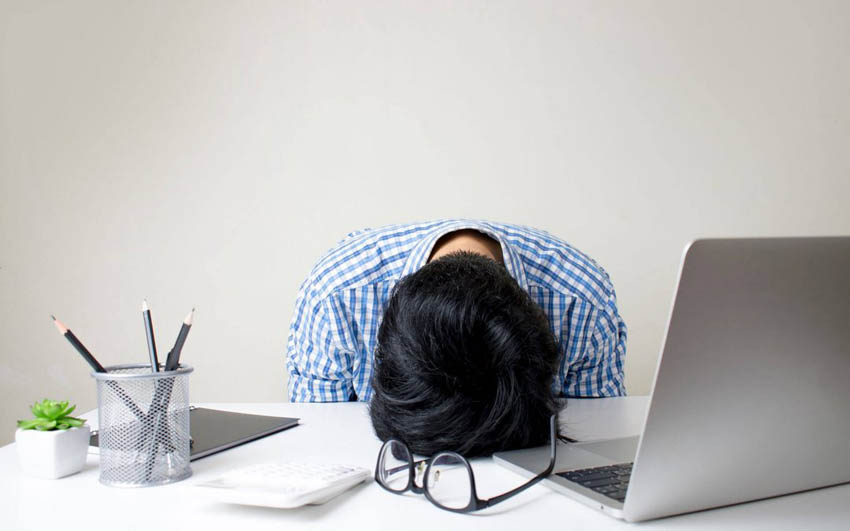 Zúfalý študent s hlavou položenou na stole