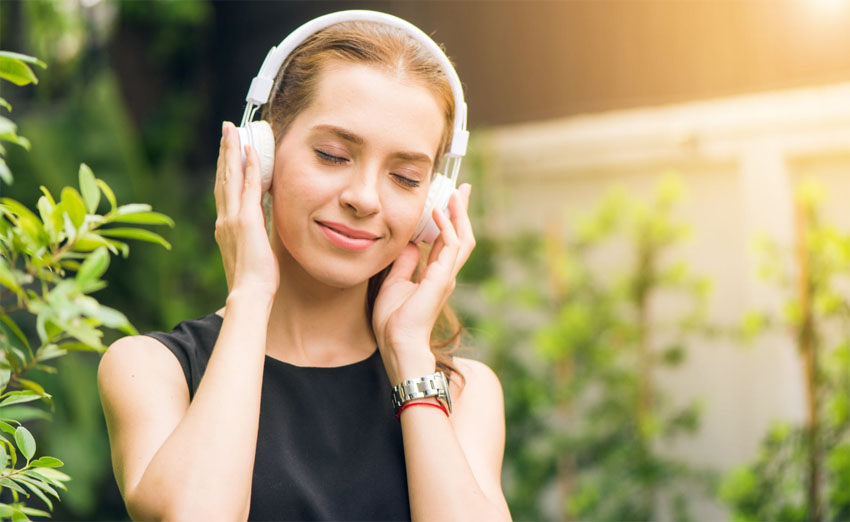 Mladá žena počúva hudbu a usmieva sa