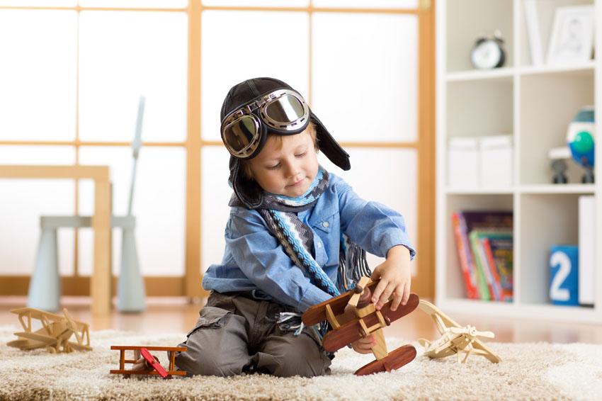 Dieťa sa hrá na pilota na koberci s lietadielkom