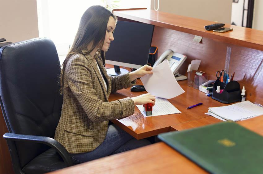 žena v kancelárii pečiatkuje dokument