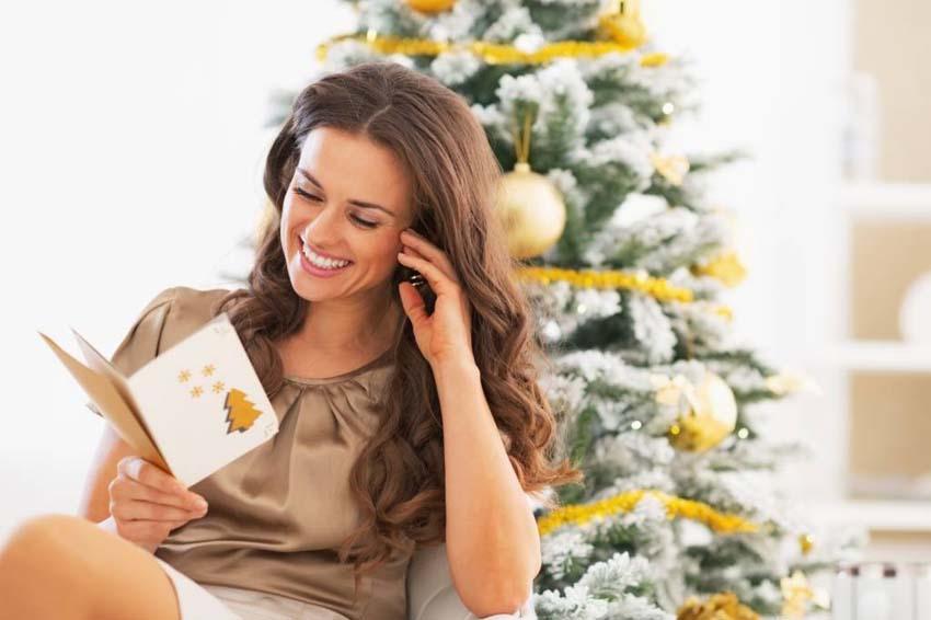 Usmievajúca sa žena čítajúca vianočnú pohľadnicu