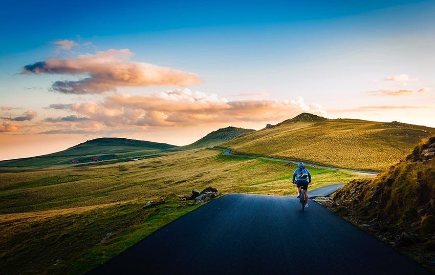 Cyklista na ceste s kopcami pred sebou