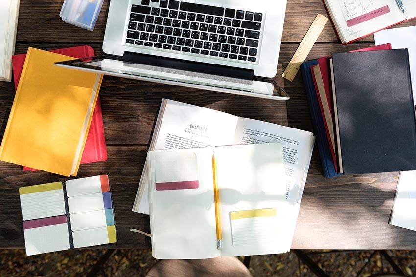 notebook, diár a knihy na stole