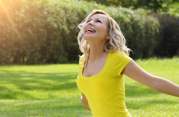 Veselá žena na lúke pozerajúca do slnka