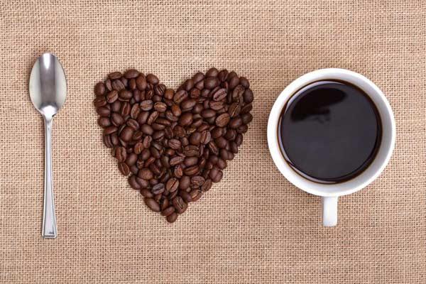 lyžička, srdiečko zo zrnkovej kávy a šálka kávy tvoriace nápis I love coffee