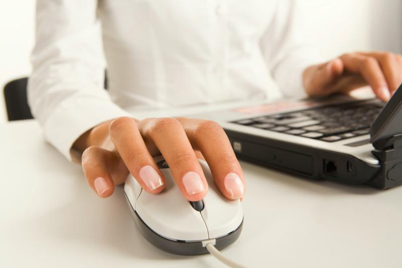 Žena píše na notebooku, detail je na ruku na myši