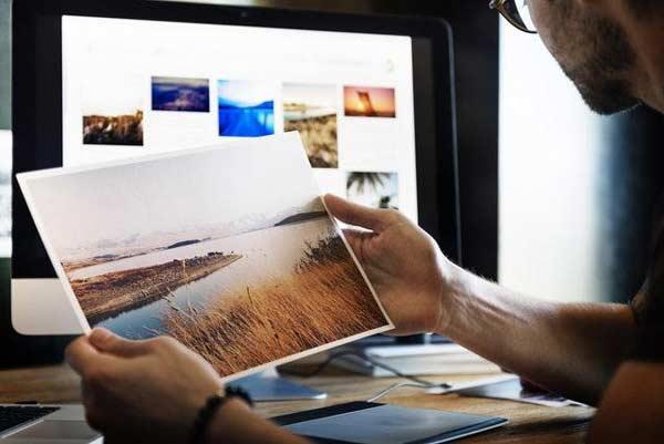 Muž si prezerá fotografie na monitore a v ruke