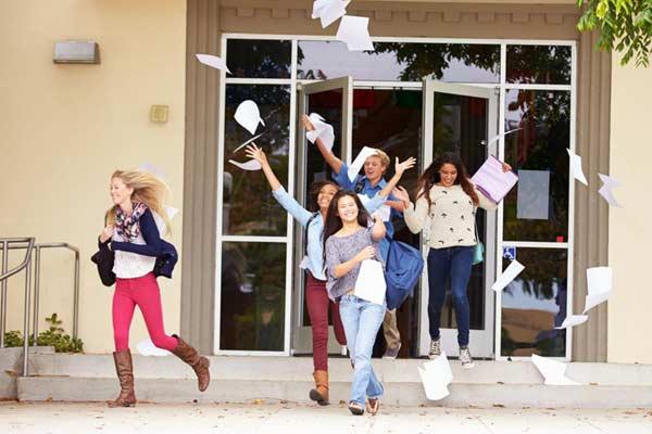 Šťastní študenti vychádzajú zo školy a vyhadzujú papiere nad hlavu