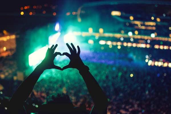 Srdiečko vytvorené z rúk v dave na koncerte