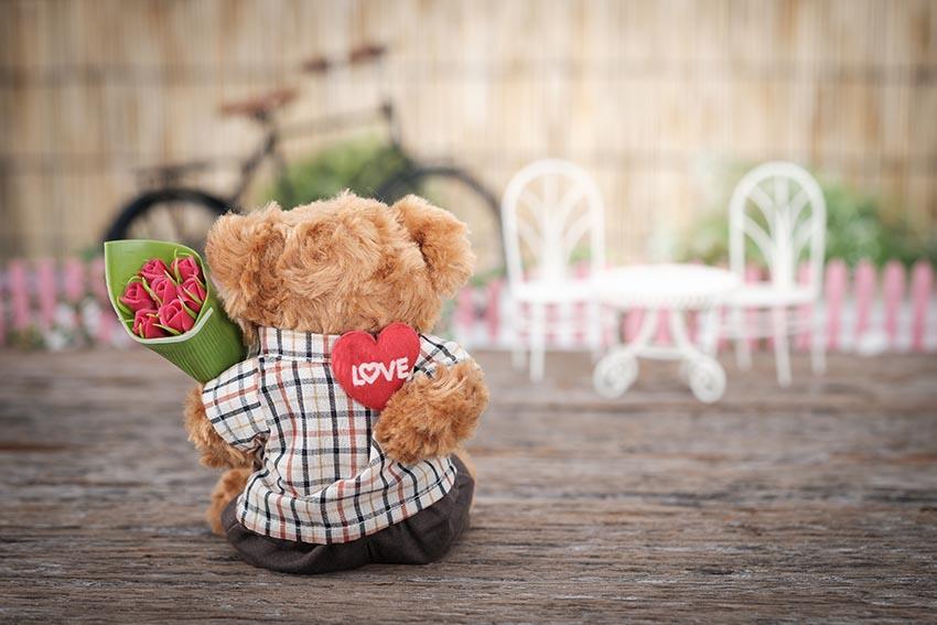 Plyšový macko obrátený chrbtom drží v ruke valentínsku kyticu a bonboniéru