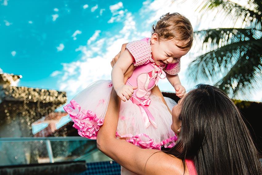 Mama drží svoje dieťa vysoko nad hlavou a smejú sa
