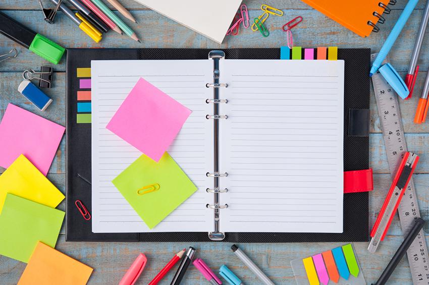 Farebné kancelárske pomôcky porozkladané na pracovnom stole v kancelárii