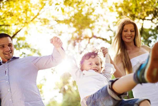 rodičia zdvíhajú syna za ruky