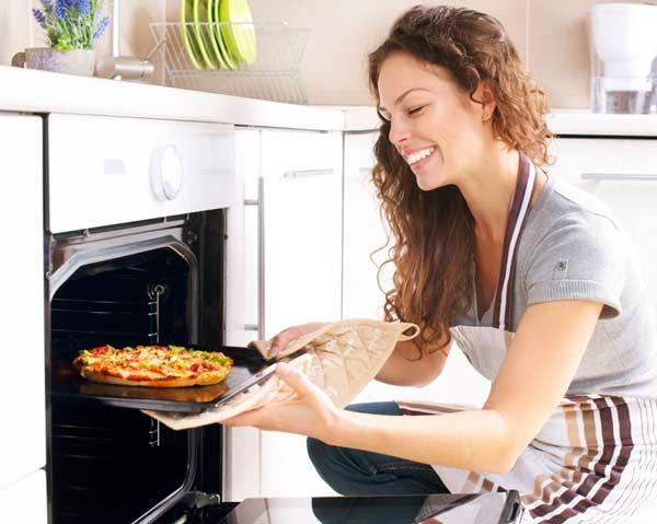 Žena vyberá z rúry pizzu